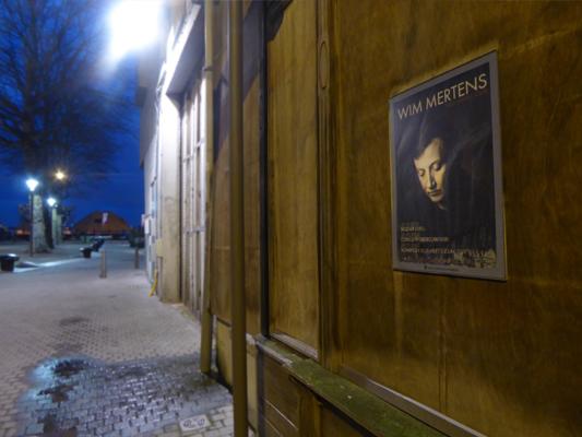 Poster van pianist, componist Wim Mertens op een winteravond in de straten van Antwerpen
