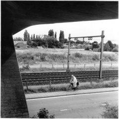 Kantoorman bij spoorbrug /  analoge dokaprint (site = scan dokaprint)